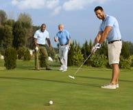 投入球的高尔夫球运动员在绿色 免版税图库摄影