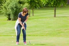 投入的妇女在高尔夫球场 免版税库存图片