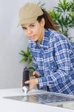 投入硅树脂密封胶的女性水管工在厨房水槽 库存图片