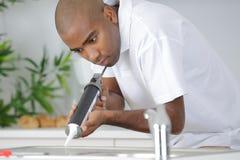 投入硅树脂密封胶的水管工对安装厨房水槽 库存照片