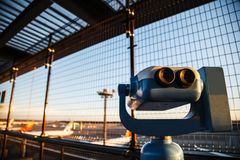 投入硬币后自动操作的双筒望远镜或望远镜游人的能观察平面起飞和装货在机场观察台 免版税库存图片