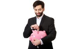 投入硬币的商人对存钱罐 免版税库存图片