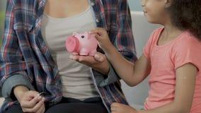 投入硬币的母亲和女儿在piggybank,财政责任,储款 股票视频