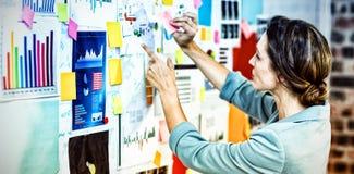 投入稠粘的笔记的女实业家在whiteboard 免版税库存照片
