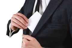 投入纸的商人在衣服口袋特写镜头 显示空白 免版税库存照片