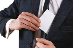 投入纸的商人在衣服口袋特写镜头 显示空白 免版税库存图片