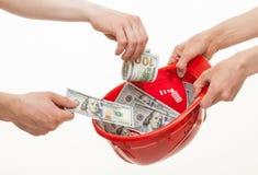 投入美元的人的手在一顶红色安全帽 库存图片