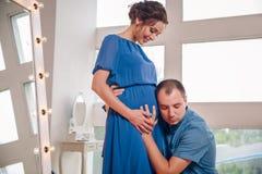 投入耳朵的愉快的年轻人对孕妇鼓起听移动的婴孩里面,接受支持的爱恋的好奇丈夫 免版税库存图片
