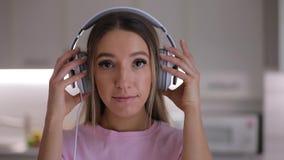 投入耳机在家听到音乐的愉快的妇女画象紧密  影视素材