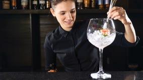 投入草莓的黑制服的女孩侍酒者在与准备鸡尾酒的冰块的玻璃 愉快的侍酒者概念 影视素材