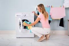 投入衣裳的妇女在洗衣机 免版税库存图片