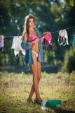 投入衣裳的比基尼泳装和衬衣的性感的深色的妇女烘干在太阳 有投入洗涤物的长的腿的肉欲的年轻女性 图库摄影