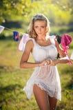 投入衣裳的湿白色短的礼服的性感的白肤金发的妇女烘干在太阳 肉欲的公平的投入洗涤物的头发年轻女性 免版税库存照片