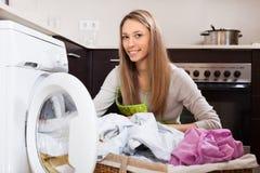 投入衣裳的白肤金发的妇女对洗衣机 免版税库存照片