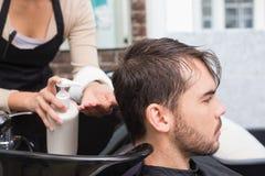 投入调节剂的美发师供以人员头发 免版税库存图片