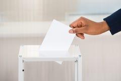 投入选票的人的手在箱子 免版税库存图片