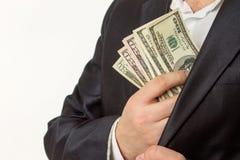 投入金钱的商人在衣服夹克口袋 免版税库存图片