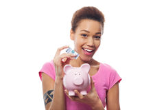 投入金钱的妇女在存钱罐中 免版税图库摄影