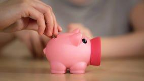 投入金钱的母亲和孩子在存钱罐,妈妈中告诉关于家庭预算 库存照片