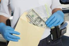 投入金钱的警察在证据信封 免版税库存图片