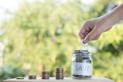 投入金钱硬币的手堆积生长,存金钱为目的概念 图库摄影