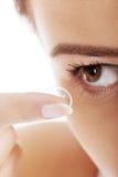 投入隐形眼镜的妇女在她的眼睛 免版税库存照片