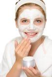 投入面部面具清洁的年轻愉快的女孩 免版税库存照片