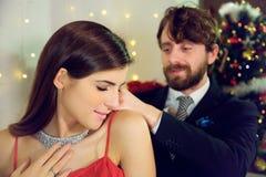 投入项链礼物的典雅的人对女朋友圣诞夜微笑 免版税库存照片