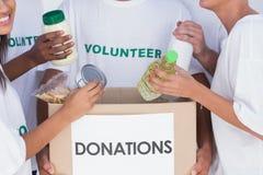 投入食物的志愿者在捐赠箱子 免版税库存图片