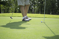 投入高尔夫球的人在高尔夫球场 免版税库存图片