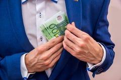投入100张欧洲票据的商人 免版税图库摄影