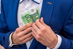 投入100张欧洲票据的商人 库存图片