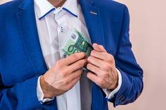 投入100张欧洲票据的商人 免版税库存照片
