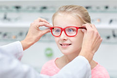 投入玻璃的眼镜师对女孩在光学商店 免版税库存照片