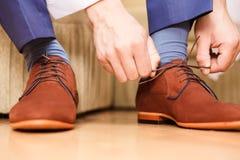投入他的婚礼鞋子的新郎 免版税图库摄影