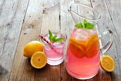 投手与被填装的玻璃的桃红色柠檬水在土气木头 免版税库存照片