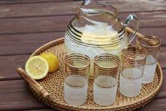 投手柠檬水和玻璃在桌上 免版税库存照片