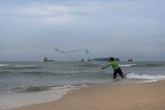 投掷一个捕鱼网的渔夫 免版税库存图片
