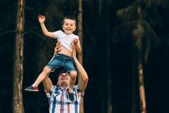 投掷他的小儿子的父亲悬而未决 一起系列时间 获得愉快的小男孩与他的爸爸的乐趣户外 免版税库存图片