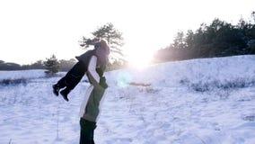 投掷他的小男孩的愉快的爸爸入在慢动作的空气和一起有乐趣时间在冬天在积雪 股票视频