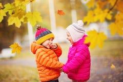 投掷叶子的孩子在美好的秋季天 库存照片