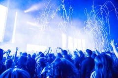 投掷在人群的Confetii大炮五彩纸屑在音乐会期间 免版税库存图片