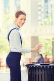投掷在回收站的女商人空的纸咖啡杯 免版税库存图片