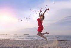 投掷在海滩的红色礼服的跳跃的美丽的妇女玫瑰花瓣 免版税图库摄影