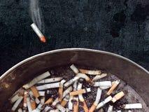 投掷在黑暗的背景的烟灰缸的灼烧的香烟 图库摄影