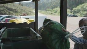 投掷垃圾的志愿者到容器 股票录像