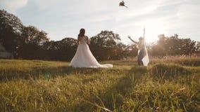 投掷婚姻的花束的愉快的新娘对太阳眨眼的女傧相 股票视频