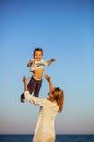 投掷小儿子在海滩的空气的愉快的少妇 免版税库存图片