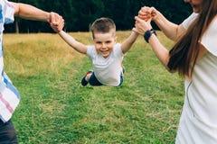 投掷小儿子的马瑟和父亲悬而未决 一起系列时间 获得愉快的小男孩与他的妈妈的乐趣和 库存图片