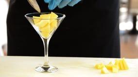 投掷模子芒果的厨师手在鸡尾酒杯结果实 影视素材